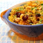 Couscous Fruit Salad - Couscous simmered with dates, raisins, and dried cranberries is a sweet accompaniment to pork or a nice fruit salad for brunch.
