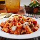 Mezzi Rigatoni with Chicken Thighs, Rosemary, Lemon Zest and Roasted Garlic Sauce - Cooked pasta is tossed with chunks of browned chicken in garlic tomato sauce with rosemary and lemon zest and topped with grated cheese.