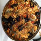 Maria's Paella-Pan Paella - Put that paella pan to use with this paella recipe featuring soft chorizo, mussels, clams, shrimp, and chicken in saffron-accented rice.