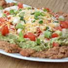 Texas Mess - Texas mess is a make-ahead dip made of a refried beans layer, avocado layer, and a sour cream layer topped with green onions, tomatoes, and Colby cheese.