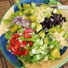 Baja Salad - Corn, black beans, avocado, and tortilla chips are tossed with romaine lettuce in a homemade lemon dressing for a Mexican-inspired chopped salad.