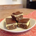 Easy Nanaimo Bars - An easy Nanaimo bar cookie uses hot cocoa mix in the crust and milk chocolate topping for a milder taste, as well as the traditional vanilla frosting middle layer. Make them in plenty of time to chill before serving.