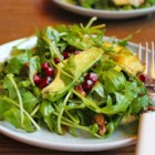 Roasted Acorn Squash Salad - Spicy baby arugula leaves make a tasty foundation for building a winter salad containing roasted acorn squash, dried cranberries, pistachios, and goat cheese in a homemade dressing with a hint of curry flavor.