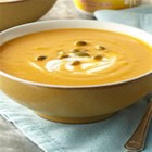 Hearty Pumpkin-White Bean Soup - Ground cumin and grated fresh ginger give this pumpkin-bean soup a touch of class. Serve the creamy blended recipe as a main dish or side dish. A swirl of yogurt and a sprinkling of pepitas (pumpkin seeds) finish the bowl.