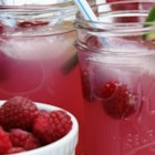 Raspberry Corona(R) Punch - Raspberries float in a mixture of lemonade concentrate, beer, and vodka in this refreshing summertime recipe.
