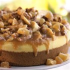 Apple Butter Cardamom Cheesecake - Traditional cheesecake is topped with apple slices cooked with apple butter, cardamom and pecans and garnished with whipped cream and crystallized ginger pieces.