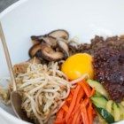 Bibimbap (Korean Rice With Mixed Vegetables) - A traditional Korean dish of rice, vegetables, fiery chile paste, and browned slices of beef is topped with a whole egg for a meal in a bowl.