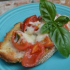 Tomato Bruschetta - Fresh tomatoes are combined with garlic, basil, and balsamic vinegar in this classic appetizer. Melted mozzarella cheese makes it extra special.