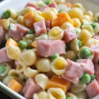 Ham and Shell Salad - Ham, peas, Cheddar cheese cubes, and shell pasta are dressed in a mayonnaise, vegetable oil, and lemon juice dressing for a nice alternative to traditional pasta salads.