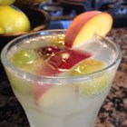 Refreshing Peach Sangria - A twist on traditional sangria uses peach schnapps, white Zinfandel wine, and pineapple juice poured over frozen peaches and grapes creating a refreshing peach sangria.