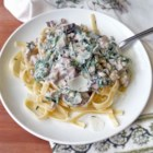 Spinach, Mushroom, and Ricotta Fettuccine - Spicy sausage, spinach, and mushrooms are sauteed in butter, mixed with ricotta cheese, and served over fettuccine in this recipe.