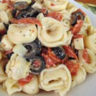 Cheese Tortellini Salad - This quick and easy picnic salad mixes cheese tortellini, pepperoni, provolone cheese, olives, and artichoke hearts with Italian-style salad dressing.