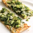 Green Pizza - This green pizza is topped with pesto, broccoli, arugula and gooey mozzarella cheese.