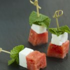 Watermelon Salad on a Stick - Impress your guests with this colorful and delicious and bite-size melon salad on a stick featuring watermelon, feta cheese, and mint!