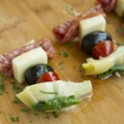 Antipasto on a Stick - Salami, mozzarella cheese, artichoke hearts, and olives are threaded on a toothpick and drizzled with olive oil for an Italian-inspired antipasto-on-a-stick appetizer.