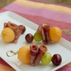 Prosciutto e Melone on a Stick - Prosciutto and cantaloupe are thread on a bamboo toothpick with red and green grapes creating a colorful and delicious appetizer!