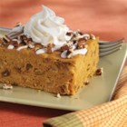 Iced Pumpkin Spice Cake - A pumpkin cake recipe with golden raisins and pumpkin pie spice topped with a white drizzle and nuts for a fall treat.