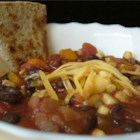 Black Bean Chili - Cooked black beans, corn, mushrooms, tomatoes, bell peppers, and onion are combined with chili powder and spices in this quick vegetarian- and vegan-friendly chili recipe.