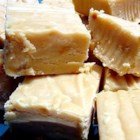 World's Best Peanut Butter Fudge - This simple recipe combines milk, butter, marshmallow cream and peanut butter, for a rich and creamy fudge you'll love.