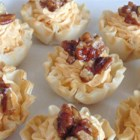 Pumpkin Cheese Tarts with Pecans and Cinnamon Sea Salt - These savory tarts with cream cheese, Cheddar, and pumpkin are topped with a pinch of cinnamon sea salt and buttery toasted pecans for an elegant holiday appetizer.