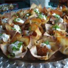 Sausage Flowers - Cups made from wonton wrappers are filled with a flavorful cheese and sausage mixture, then baked and topped with sour cream and chopped green onions.