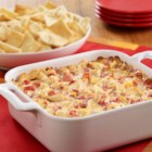 Creamy Artichoke Dip - A warm cheesy dip recipe brimming with artichoke hearts and tomatoes to serve on pita chips or sliced French bread.