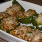 Stuffed Peppers - Green bell peppers are filled with ground beef, cooked rice, tomato sauce, and seasonings, then baked for an hour with additional tomato sauce and Italian-style seasoning.