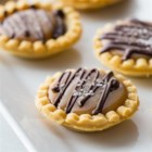 Mini Salted Caramel Chocolate Pies - Mini tart shells filled with layers of caramel and ganache are drizzled with more dark chocolate and topped with sea salt crystals for an elegant dessert.