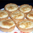 Milk Tart - The sugary crust dough is pressed into the pie tin and baked. The sweet, milky thick custard filling is then poured into the baked shell, sprinkled with cinnamon and chilled. Makes two lovely pies.