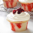 White Chocolate-Cranberry Poke Cupcakes - Topped with white chocolate cream cheese frosting and dried cranberries, these poke cupcakes are as festive looking as they are scrumptious.