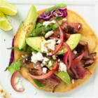 Steak Taco - Slices of grilled flank steak are served on tortillas with avocado, pickled onions, lettuce, and cabbage.