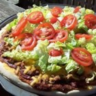 Taco Pizza - Pizza dough prepared in the bread machine is topped with refried beans, salsa, seasoned beef, and cheddar cheese.