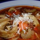 Charlotte's Tortellini Soup - Zucchini slices and diced red peppers float with tortellini in a beef and sausage broth in this tomato-based soup.  Serve with a sprinkling of grated Parmesan.