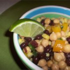 Mexican Salad - Black beans, garbanzos, and corn are tossed with assorted vegetables in a cilantro-lime vinaigrette in this versatile salad.  Serve plain, rolled and warmed in tortillas or as an appetizer with corn tortilla chips.