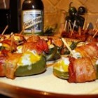 Sausage Jalapeno Poppers - Jalapeno pepper slices are stuffed with a sausage and cream cheese mixture, then wrapped with bacon. They're a spicy, mouthwatering party favorite! Secure the bacon with toothpicks.