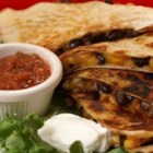 Black Bean and Corn Quesadillas - These black bean and corn quesadillas are really cheesy, a little bit spicy, and a little bit sweet.  My vegetarian husband goes crazy over these every time!  Feel free to play around and add chicken or veggies, if you desire.  Don't forget the salsa and sour cream!