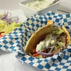 Traditional Gyros - Make your own traditional gyros at home by layering homemade gyro meat, hummus, tzatziki sauce, tomatoes, and feta cheese on a large pita bread.