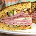 Real N'awlins Muffuletta - A homemade olive salad is spread on fresh bread which is then layered with salami, ham, mortadella, mozzarella and Provolone. Great sandwich, anyone?! Note: Use round bread loaves for real muffuletta.
