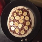 "Banana-Nutella(R) Tortilla Pizza - Make a dessert ""pizza"" using a tortilla topped with Nutella(R) and bananas for a fun and tasty treat adults and kids will love."