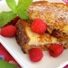 PBJ French Toast - A peanut butter and jelly sandwich is dipped in a raspberry liqueur-infused batter and pan-fried into a peanut butter and jelly French toast treat.