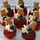 Strawberry Graham Cracker Bites - Strawberries filled with whipped cream and Nutella(R) are topped with a mini graham cracker for a colorful treat on the 4th of July.