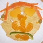 Edible Face - Cheddar, cherry tomatoes, carrot, oranges and crackers are cut and arranged to make a face children will love to eat.