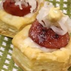 Mini Sausage Reubens - Puff pastry cups are filled with shredded Swiss cheese, slices of kielbasa, sauerkraut, and Dijon for mini bites of a classic Reuben sandwich.