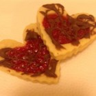 Old Fashioned Butter Valentine Cookies Dipped in Chocolate - Tender, heart-shaped butter cookies are filled with raspberry jam and drizzled with a little bit of chocolate for a deliciously sweet Valentine.