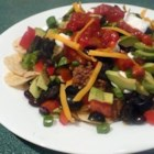 Taco Nachos - This straightforward nacho recipe is sure to please. Ground beef and cheese are melted over chips to create a gooey, messy and delicious snack.