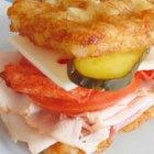 "The Super Sandwich - Tomato, pickles, ham, Swiss cheese, potato chips, bacon, and turkey are sandwiched between two slices of ""bread"" made from Tater Tots(R)."