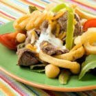 Philly Steak Salad - The cheesy, juicy goodness of a Philly cheese steak is piled atop crunchy curly fries and cool, crispy salad greens in this richly satisfying salad.