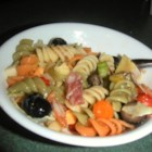 Ellen's Muffaletta Pasta Salad - New Orleans' famous muffaletta sandwich is translated into a pasta salad with this recipe packed with vegetables, meat, and cheese for a unique Mardi Gras party item.