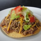 Crispy Oven Beef-and-Bean Tostadas - Bake corn tortillas to get crispy tostadas in this recipe for a homemade version of a Mexican favorite topped with seasoned ground beef and refried beans.