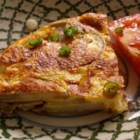 Spanish Potato Omelet - There's nothing too fancy about this rustic Spanish style omelet, just lots of hearty goodness from crispy fried potatoes and onions. Chopped tomatoes and green onions lend even more flavor and color.